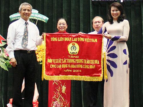 Ông Đặng Ngọc Tùng, Chủ tịch Tổng LĐLĐ Việt Nam, trao cờ thi đua xuất sắc của Tổng LĐLĐ Việt Nam cho tập thể Thường trực LĐLĐ TP HCM Ảnh: HOÀNG TRIỀU