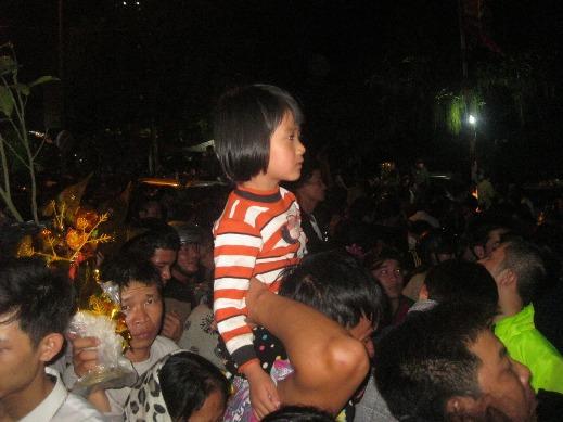 Cháu bé được bố cõng trên vai giữa đám đông chen chúc ngạt thở