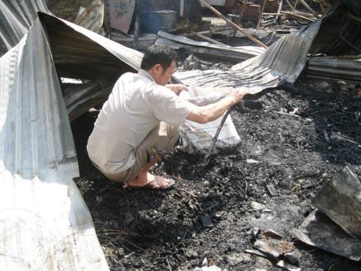 Người đàn ông tìm những đồ còn sót lại sau vụ cháy