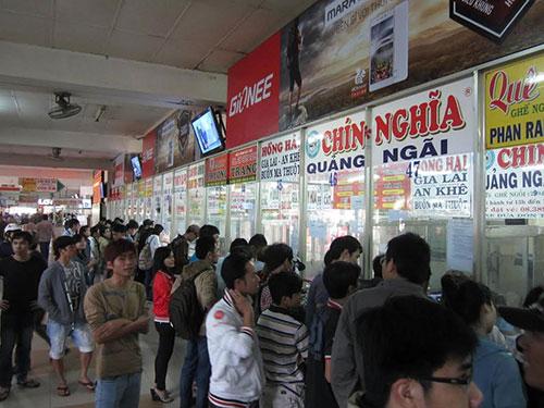 Hành khách mua vé xe Tết 2015 tại Bến xe Miền Đông. Nhiều hãng xe đi tuyến miền Bắc, miền Trung chưa giảm giá theo xăng mà đã tăng giá vé Tết Ảnh: GIA MINH
