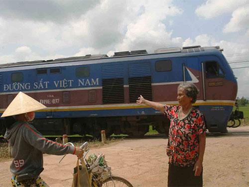 Ông Nguyễn Văn Ca (trên) và bà Ngô Thị Hoa hằng ngày tự nguyện ra đường ngang cảnh giới tàu hỏa cho người qua lại