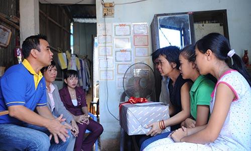 Diễn viên Quyền Linh - đại sứ chương trình đi bộ từ thiện Lawrence S. Ting đang thăm hỏi và trao quà cho chị Lê Thị Ngọc Hương- huyện Bình Chánh