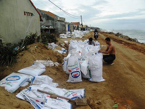 Lo mất nhà, người dân xóm Rớ phải tự làm kè bằng bao cát để chắn sóng
