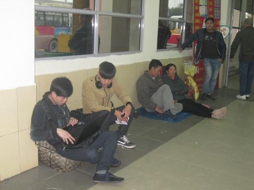 Hành khách tìm tạm nơi nghỉ ngơi chờ tới lượt mua vé