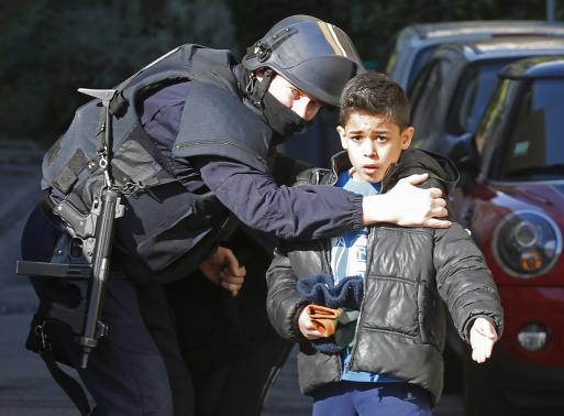...trong khi cảnh sát hướng dẫn một cậu bé sơ tán. Ảnh: Reuters