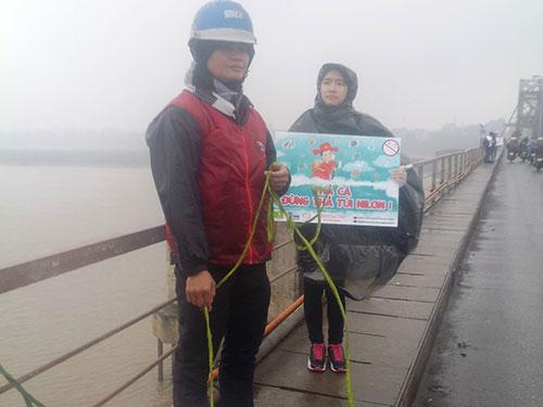 Sinh viên tình nguyện trong nhóm Cá Chép đứng ở cầu Long Biên hướng dẫn, giúp đỡ người dân thả cá mà không thả túi ni-lông xuống sông và gom rác tại cầu