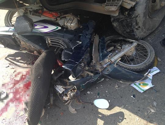 Chiếc xe máy hư hỏng nằm kẹt dưới gầm xe ben