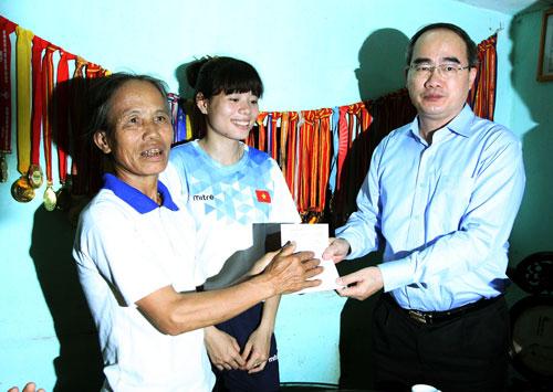 Chủ tịch Ủy ban Trung ương MTTQ Việt Nam Nguyễn Thiện Nhân tặng quà cho gia đình Nguyễn Thị Huyền Ảnh: TTXVN