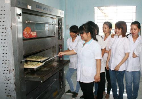 Cô Lê Hoàng Thanh Vy, giáo viên Khoa Công nghệ thực phẩm, hướng dẫn sinh viên làm bánh trong giờ thực hànhẢnh: LỘC TRẦN