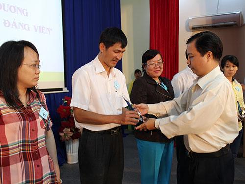 Ông Ma Xuân Việt - Phó Bí thư Thường trực Quận ủy quận Tân Bình, TP HCM - tặng biểu trưng cho các gương sáng đảng viên
