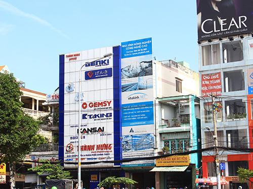 Hai tấm biển quảng cáo lớn án ngữ che phủ hết toàn bộ 2 căn nhà liền kề trên đường Xuân Diệu (phường 4, quận Tân Bình)