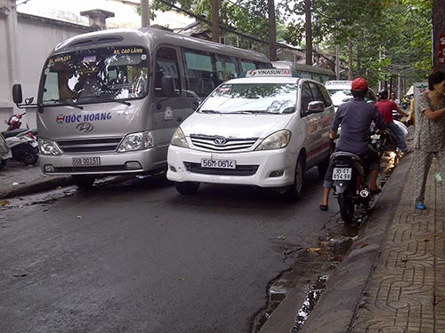 Đường Phạm Hữu Chí (quận 5) chật chội khi bị 2 chiếc xe khách đỗ bên đường choán chỗ