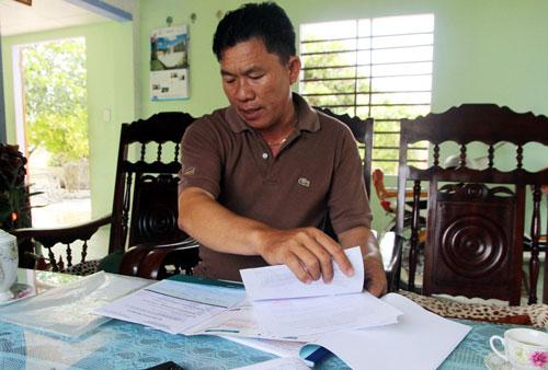 Ngư dân Phan Thu bên mớ hồ sơ vay vốn ngân hàng để đóng tàu Ảnh: Trần Thường