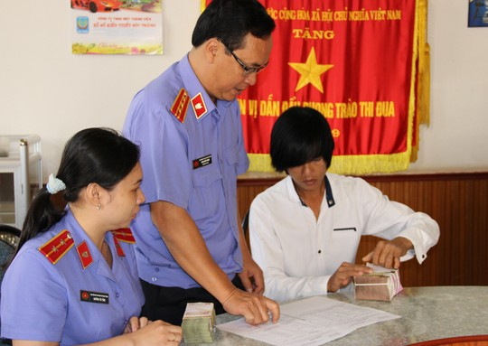 Trần Văn Đỡ đang nhận tiền từ VKSND tỉnh Sóc Trăng - ảnh PHẠM CÔNG