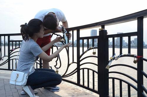 Một đôi nam nữ móc ổ khóa vào thành cầu, cùng ước nguyện tình yêu bền chặt