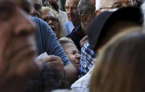 Người về hưu chen nhau trước một chi nhánh Ngân hàng Quốc gia ở Athens hôm 1-7 Ảnh: REUTERS