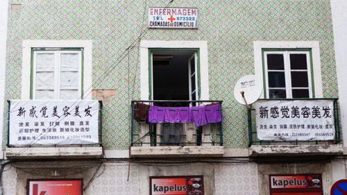 Các biển hiệu bằng chữ Trung Quốc treo phía trước nhà dân gần quảng trường Martim Moniz tại thủ đô Lisbon - Bồ Đào Nha Ảnh: Bloomberg