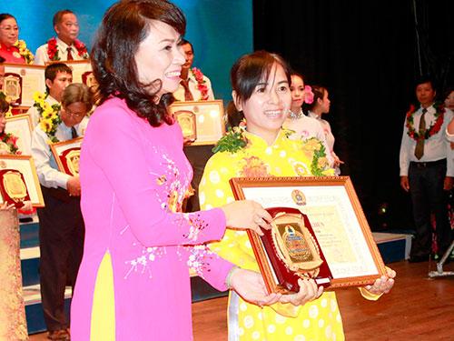 Bà Nguyễn Thị Thu - Thành ủy viên, Chủ tịch LĐLĐ TP HCM - trao biểu trưng cho cá nhân điển hình Ảnh: KHÁNH AN