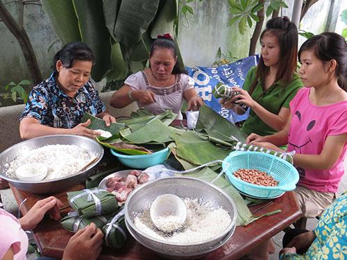 Bà chủ nhà trọ Lê Thị Thanh Hoa (thứ hai từ trái sang) cùng gói bánh tét với công nhân