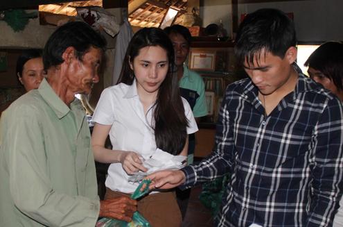Vợ chồng Công Vinh tặng quà cho một người nghèo ở một ngôi chùa tại TP HCM