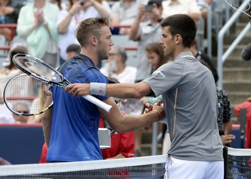 Jack Sock không thể gây sốc trước Novak Djokovic (phải)