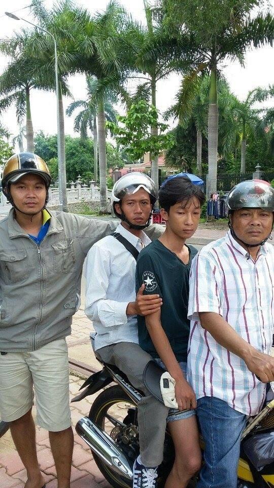 """Nguyễn Quốc Thông (ngồi giữa xe), bị các """"hiệp sĩ"""" khống chế chở về công an vào trưa 6-7."""