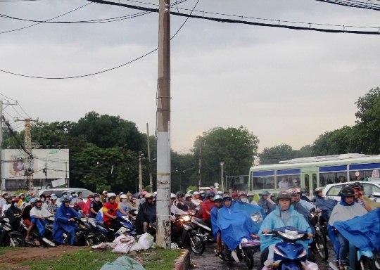 Tại vòng xoay Phạm Văn Đồng - Nguyễn Kiệm (quận Gò Vấp), giao thông ùn ứ nghiêm trọng và càng hỗn loạn hơn khi cơn mưa tiếp tục đổ xuống vào giờ tan tầm