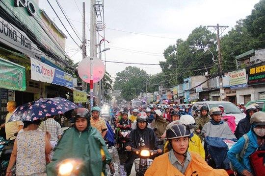 Đường Nguyễn Kiệm hướng từ ngã tư Phú Nhuận về quận Gò Vấp ùn tắc nghiêm trọng. Dòng xe ô tô nối đuôi nhau, nhích từng chút để di chuyển trong khi người đi xe máy phải leo lên vỉa hè để lưu thông