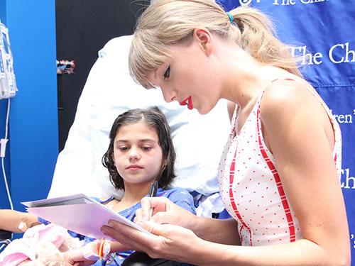 Taylor Swift thăm hỏi và tặng chữ ký cho một bệnh nhi ở Bệnh viện Philadelphia  Ảnh: CHILDREN'S HOSPITAL OF PHILADELPHIA