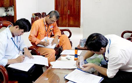 Nhân viên Điện lực Biên Hòa đang kiểm tra và lập biên bản một trường hợp vi phạm sử dụng điện năm 2014 (ảnh minh họa). Ảnh tư liệu