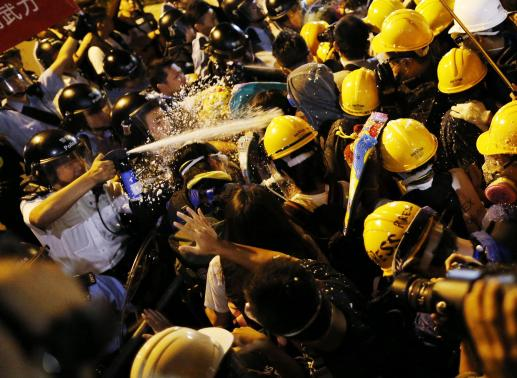 Police use pepper spray during clashes with pro-democracy protesters close to the chief executive office in Hong Kong in this November 30, 2014 file photo.  REUTERS-Tyrone Siu-File