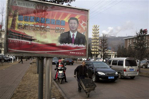 In this Feb. 6, 2015 photo, a motorcyclist uses his mobile phone near a billboard showing Chinese President Xi Jinping with the slogan