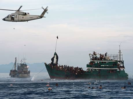 Rohingya migrants swim to collect food supplies dropped by a Thai army helicopte