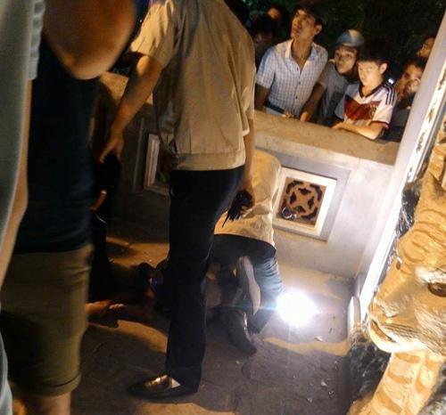 Người đàn ông đập bát hương dưới chân Bút Tháp đang bị lực lượng bảo vệ khống chế - Ảnh: CTV