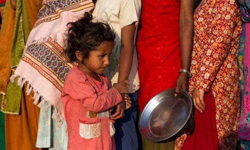 Một đứa bé nép mình cạnh mẹ giữa dòng người xếp hàng nhận lương thực ở Kathmandu - Nepal Ảnh: EPA
