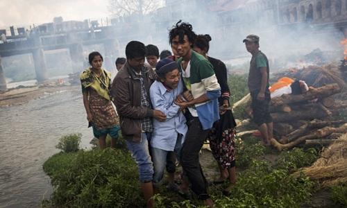Một người đau khổ trong lễ hỏa táng người thân. Ảnh: AP