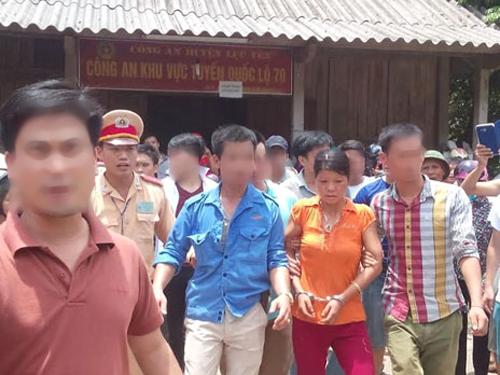 Cô gái Nguyễn Thị Hán (áo cam, bị còng tay) bị bắt cùng nghi can Đặng Văn Hùng đang được dẫn giải về Công an huyện Văn Yên - Ảnh: VNE