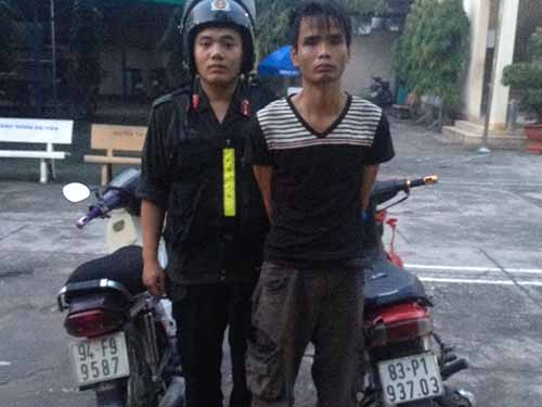 Bùi Quang Thái (phải) bị bắt giữ vì hành vi trộm xe máy vào rạng sáng 8-10-2014