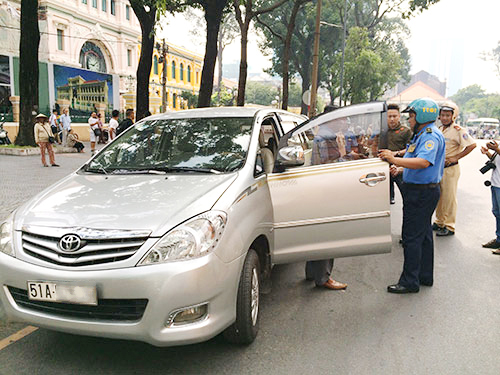 Thanh tra giao thông TP HCM lập biên bản xử phạt hành chính 1 tài xế xe Uber - Ảnh: Hải Phong