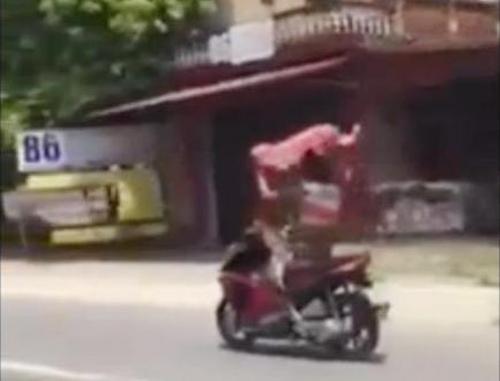 Nam thanh niên giơ cao 2 tay cầm áo che nắng, lái xe bằng chân - Ảnh cắt từ clip