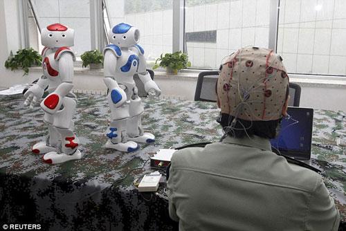 Sinh viên IEU đang thử nghiệm công nghệ điều khiển robot bằng ý nghĩ  Ảnh: Reuters