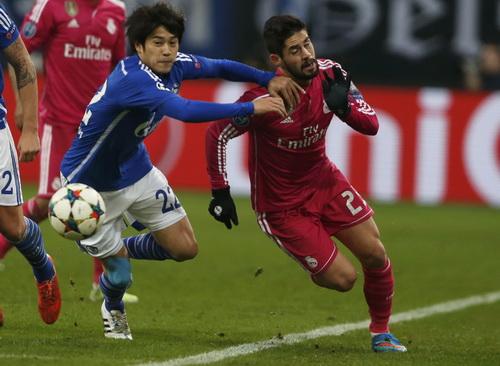 Isco (trái) đi bóng trước sự truy cản của Uchida phía Schalke