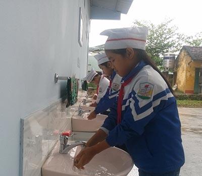 Học sinh tiểu học đang vệ sinh cá nhân tại trường