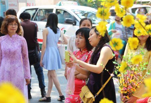 Nhiều chị em trong trang phục truyền thống xem hoa, chụp ảnh lư niệm tại học hoa ở đường Phạm Ngọc Thạnh, quận 1 (khu vực Nhà văn hóa Thanh niên)