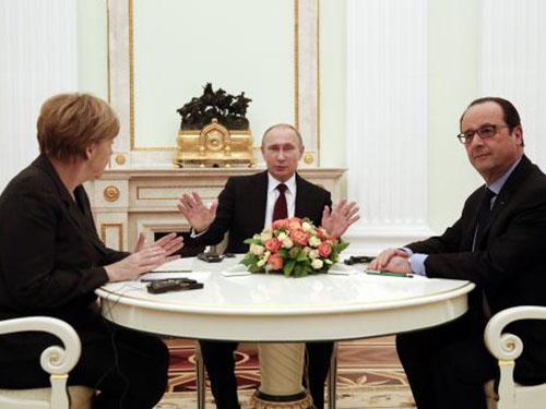 Thủ tướng Đức Angela Merkel, Tổng thống Nga Vladimir Putin và Tổng thống Pháp Francois Hollande (bìa phải) hôm 6-2 Ảnh: REUTERS