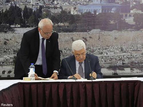 Tổng thống Palestine Mahmoud Abbas (phải) ký các thỏa thuận quốc tế tại TP Ramallah hôm 31-12-2014 Ảnh: Reuters