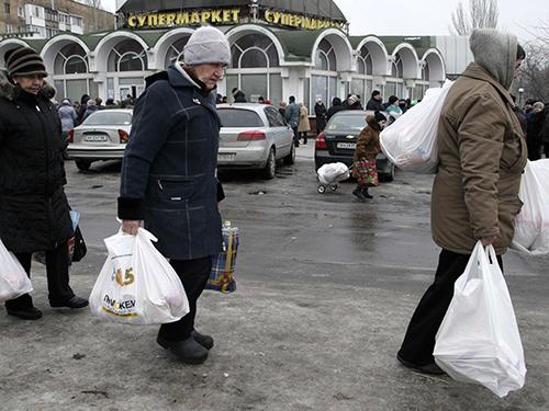 Người dân địa phương xách những gói hàng cứu trợ tại TP Donetsk, miền Đông UkraineẢnh: REUTERS