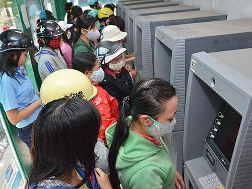Các máy ATM quanh KCX Tân Thuận, TP HCM luôn thu hút lượng lớn công nhân đến rút tiền mỗi ngày. Ảnh: Tấn Thạnh
