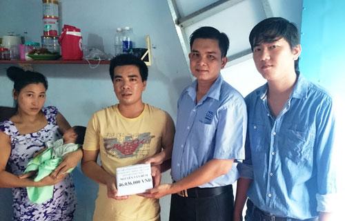Đại diện Công đoàn Công ty TNHH May mặc Triple Việt Nam (bìa phải) trao tiền hỗ trợ vợ chồng anh Nguyễn Văn Hùm