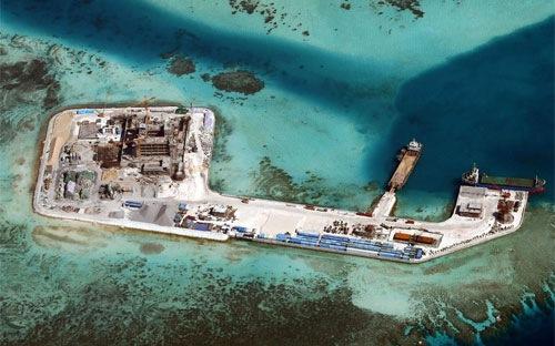 Trung Quốc đang xây dựng trái phép một đường băng trên bãi đá Chữ Thập sau khi bồi đắp bãi đá này - Ảnh: EPA/Bloomberg